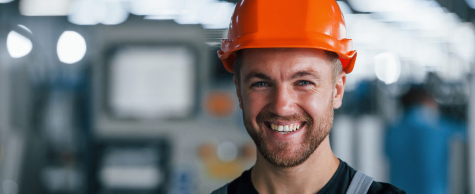 Smiling and happy employee. Portrait of industrial worker indoors in factory. Young technician with orange hard hat.